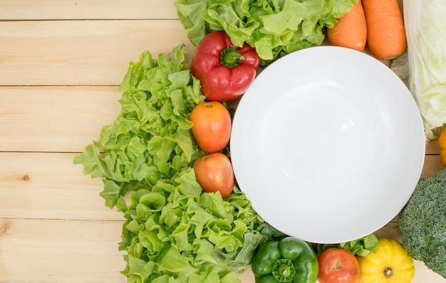 De lege schotel rond met de tomaten, paprika's, wortelen, maïs, pompoen en slagroente