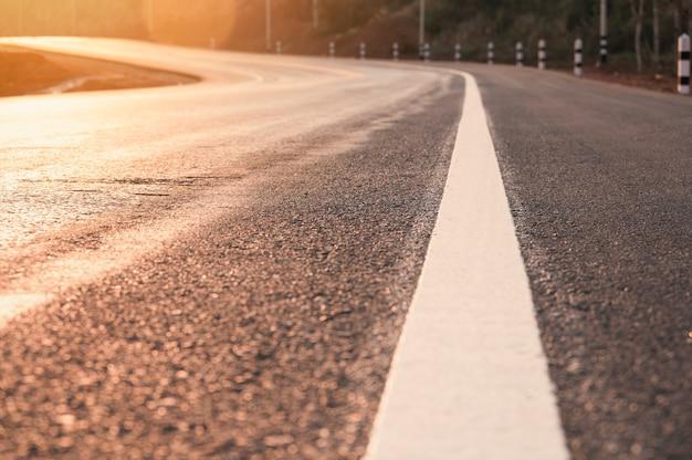 De lege weg van de asfaltkromme op platteland bij zonsonderganglicht