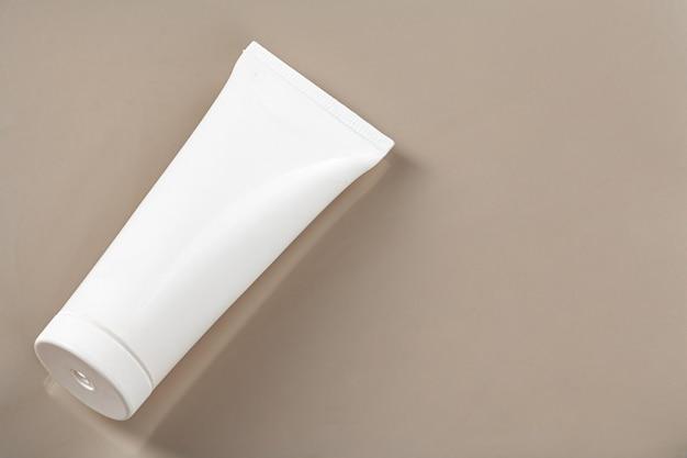 De lege witte buis van het huidverzorgingsproduct op beige achtergrond met exemplaarruimte