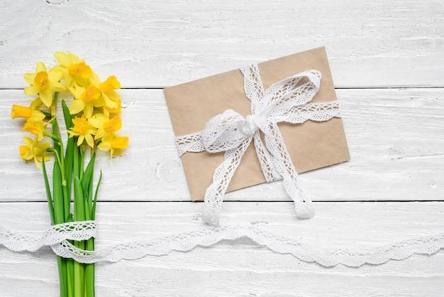 De lege witte groetkaart en de envelop met lente gele narcissen bloeien boeket over witte houten lijst