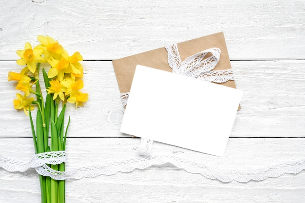 De lege witte groetkaart met de lente gele narcissen bloeit boeket over witte houten lijst.