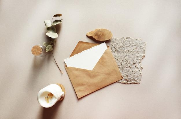 De lege witte modellen van de uitnodigingskaarten van de huwelijksgroet met ambachtenvelop, droge eucalyptusbladeren op geweven lijst backgound. elegante moderne sjabloon voor branding identiteit. plat lag, bovenaanzicht