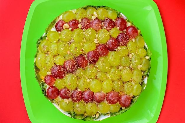 De legendarische tiffany gelaagde salade met druiven, kip en kaas op de rode achtergrond. het dankt zijn naam aan de bijnaam van de dame die het recept van de salade op het culinaire portaal plaatste.