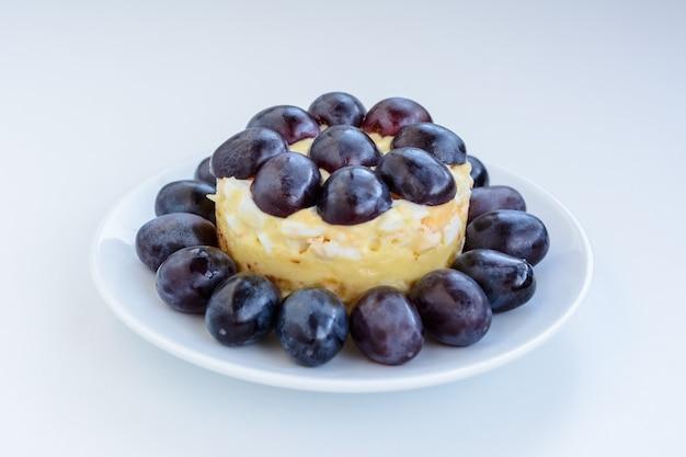 De legendarische tiffany gelaagde salade met druiven, kip en kaas op de witte achtergrond. het dankt zijn naam aan de bijnaam van de dame die het recept van de salade op het culinaire portaal plaatste.