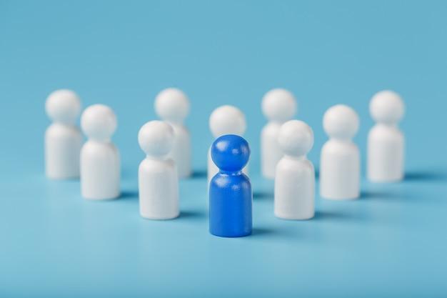 De leider in het blauw leidt een groep blanke medewerkers naar overwinning, hr, personeelswerving. het concept van leiderschap.