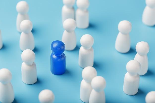 De leider van de blauwe kleur staat tussen de menigte, een groep witte werknemers. het concept van leiderschap. veel werknemers voelen zich aangetrokken tot hun baas. selectie van personeel.