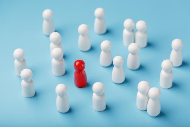 De leider van de rode kleur staat tussen de menigte, een groep witte werknemers. het concept van leiderschap. veel werknemers voelen zich aangetrokken tot hun baas. selectie van personeel.