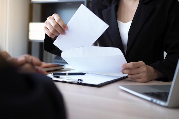 De leidinggevenden openen de envelop van ontslag van het personeel. ontslag uit vacatures en vacatures concept