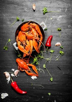 De lekkernijen. gekookte langoesten met kruiden en pikante pepers. op een zwart bord.