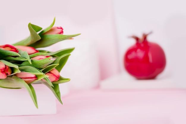 De lente bloeit rode tulpen en keramisch granaatappelfruit