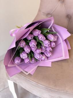 De lente is een delicaat boeket van lila tulpen. paarse bloemen voor een romantisch cadeau in een bloemenwinkel