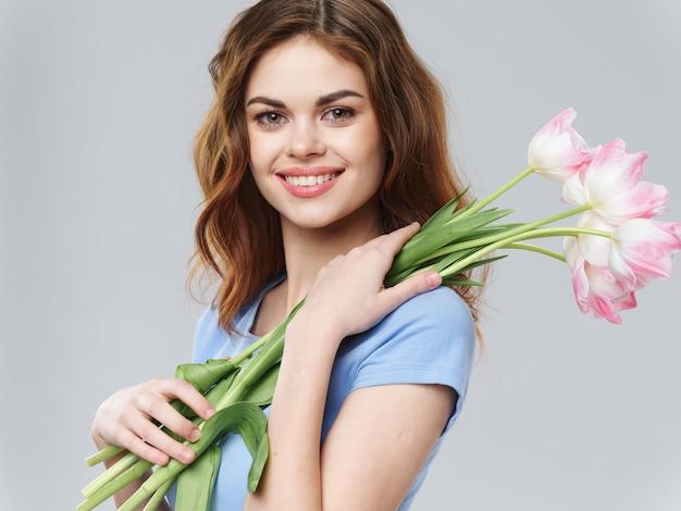 De lente jong mooi meisje met bloemen op een gekleurde achtergrond, vrouw het stellen met een boeket van bloemen, vrouwendag