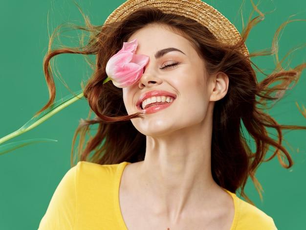 De lente jong mooi meisje met bloemen op het gekleurde, vrouw stellen met een boeket van bloemen, vrouwendag