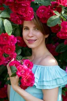 De lente. sluit omhoog portret van een gelukkig mooi roodharigemeisje met charmante glimlach die trendy blauwe lichte kleding op een aard van bloeiende rozen dragen. buitenshuis.