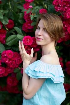 De lente. sluit portret aantrekkelijke roodharige jonge vrouw die modieuze blauwe lichte kleding dragen die bloeiende rozen in de tuin ruiken. buitenshuis.
