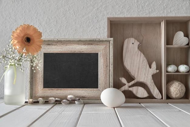 De lenteachtergrond: bord, vertoningskabinet met pasen-decoratie en gele gerbera, tekst