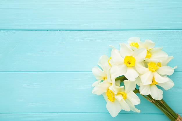 De lenteboeket van narcissen op blauwe houten achtergrond