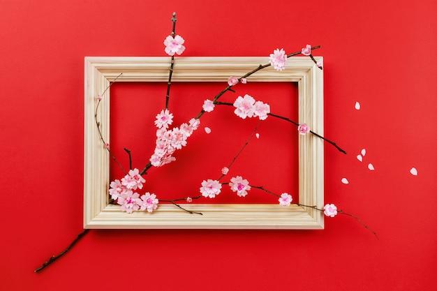 De lentesamenstelling met boomtak met document sakurabloemen door houten frame op rood