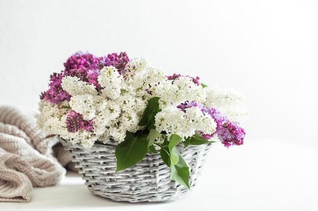 De lentesamenstelling met gekleurde lila bloemen in een rieten mand. ruimte voor tekst. geschenkmanden en bloemenleveringsconcept.