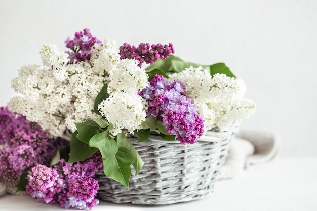 De lentesamenstelling met gekleurde lila bloemen in een rieten mand.