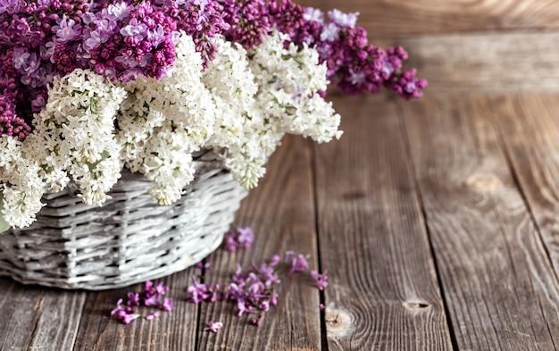 De lentesamenstelling met lila bloemen in een rieten mand. geschenkmanden en bloemenleveringsconcept.