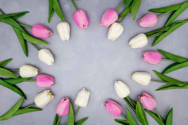 De lentesamenstelling met tulpen op geweven grijs