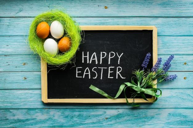 De lentesamenstelling voor de paasvakantie. eieren in het nest, krijtbord met een wens. bloemen.
