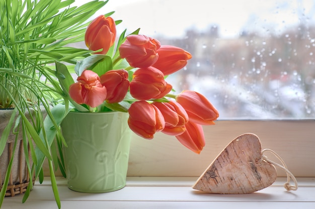 De lentetafel met groen gras, bos van oranje tulpen en houten hart op vensterraad