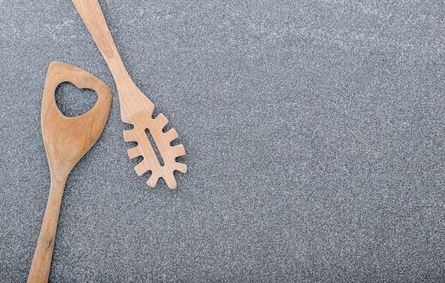 De lepellepel en spatel van deegwaren op donkere granietachtergrond met exemplaarruimte.