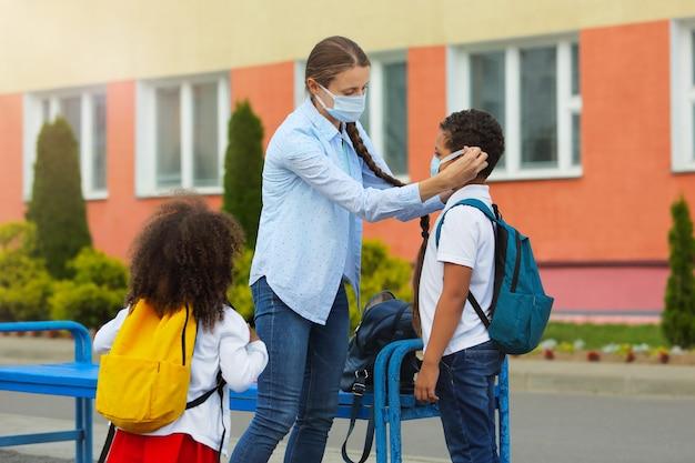 De leraar controleert de juistheid van het dragen van een zwart jongensmasker om een coronavirus of een verkoudheid te voorkomen