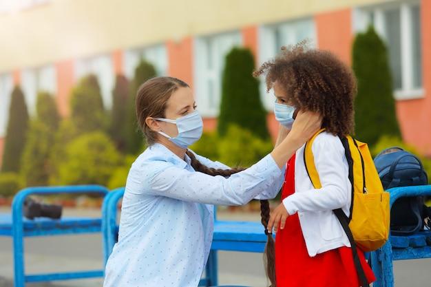De leraar controleert de juistheid van het dragen van een zwart meisjesmasker om een virus of verkoudheid te voorkomen