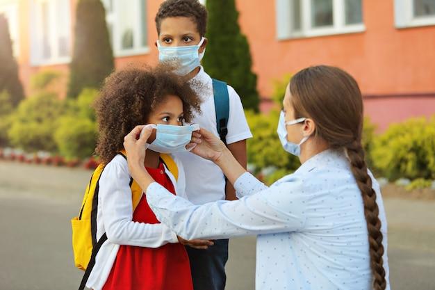 De leraar controleert en helpt het meisje om het masker correct op te zetten om coronavirus te voorkomen