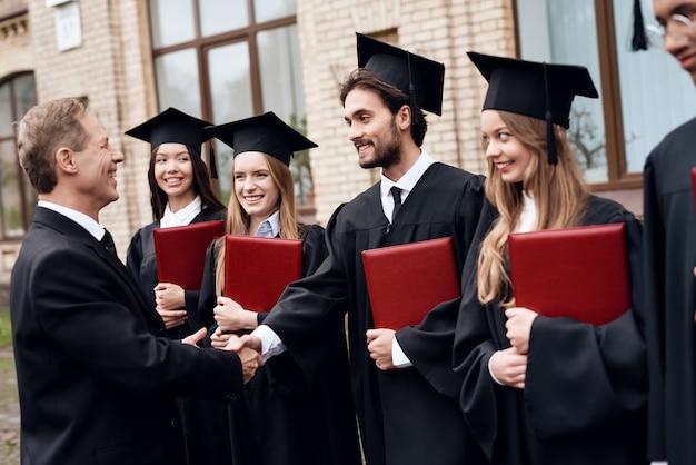 De leraar geeft de studenten diploma's op de binnenplaats