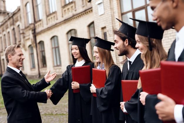 De leraar geeft de studenten diploma's.