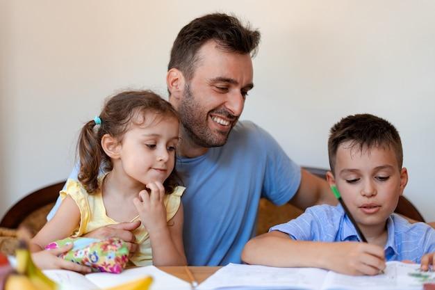 De leraar helpt zijn studenten om taken uit het schoolboek op te lossen, verheugt zich in het succes van zijn studenten. twee kinderen lossen samen met de leraar de taak van de basisschool op.