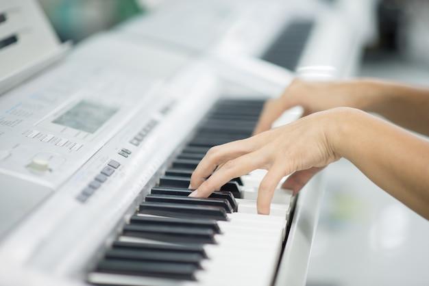 De leraar leert toetsenbord electone instument aan een jongen in klassenruimte