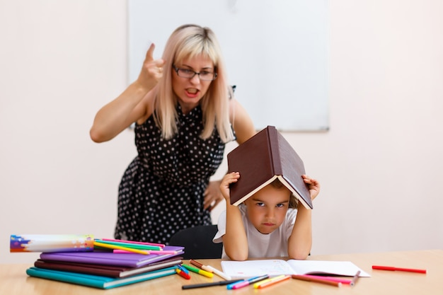 De leraar schreeuwt naar het kleine schoolmeisje