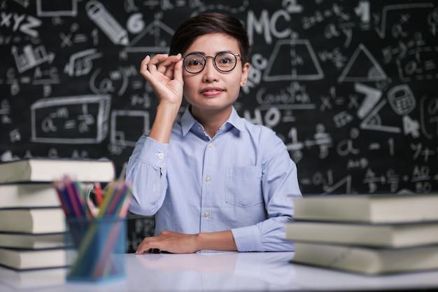 De leraar zat aan tafel en hield de bril vast in de klas.