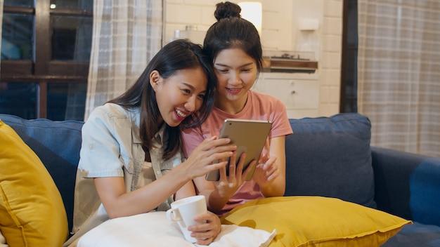 De lesbische lgbtvrouwen koppelen thuis het gebruiken van tablet