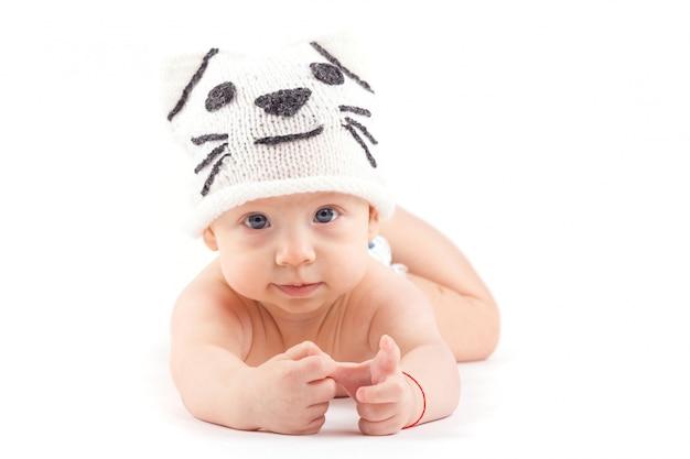 De leuke aantrekkelijke babyjongen in luier en kattenhoed ligt op buik