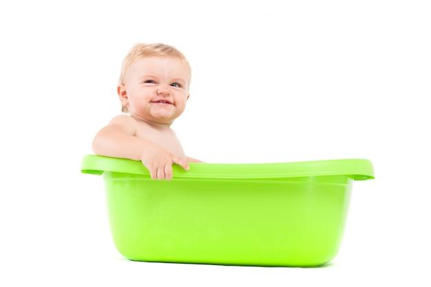 De leuke aantrekkelijke babyjongen neemt bad in ton