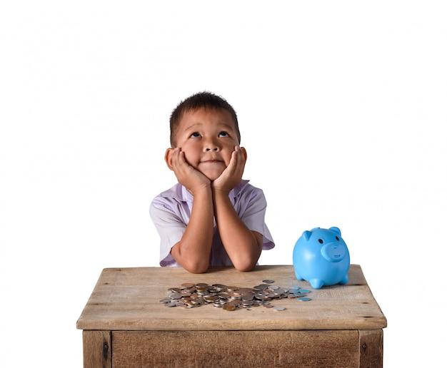 De leuke aziatische die jongen van het land heeft het denken met spaarvarken en muntstukken op witte achtergrond wordt geïsoleerd