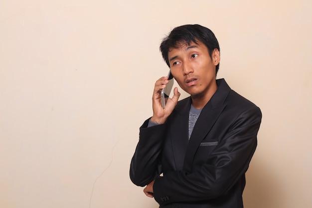De leuke aziatische jonge mens met luie uitdrukking neemt een telefoongesprek op, dat een kostuum met een swea draagt
