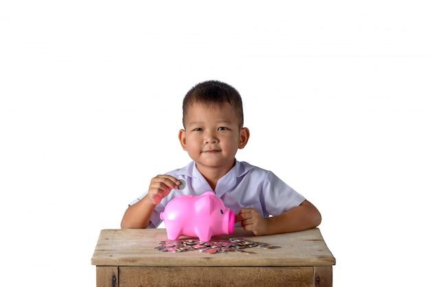 De leuke aziatische jongen die van het land muntstukken zetten in geïsoleerd spaarvarken op witte achtergrond