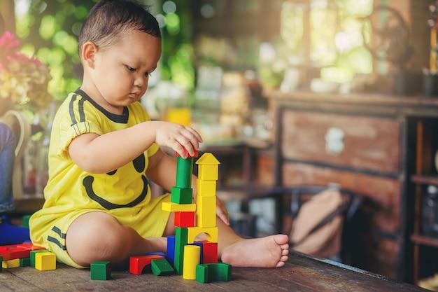 De leuke aziatische jongen is van plan om met kleurrijk houten blok te spelen. opleiding