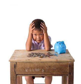 De leuke aziatische jongen van het land heeft hoofdpijn met spaarvarken en muntstukken