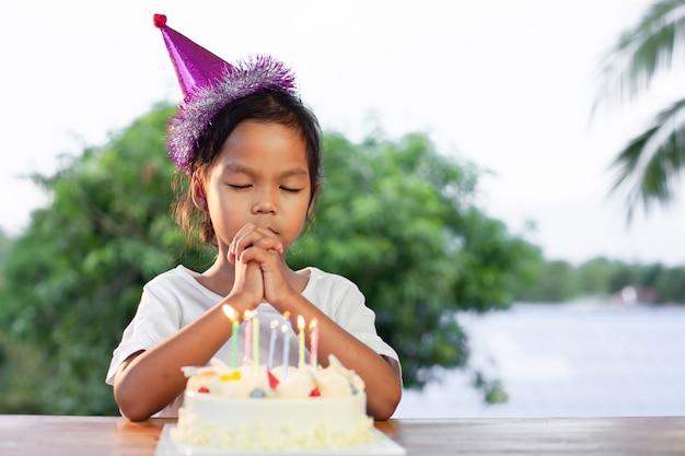 De leuke aziatische kindmeisjes maken gevouwen hand om de goede dingen voor haar verjaardag in verjaardagspartij te wensen