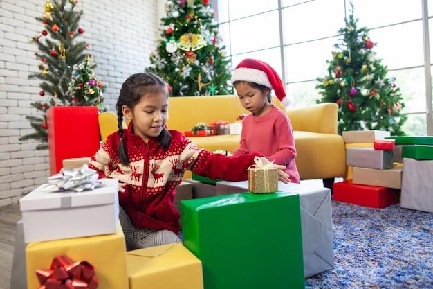De leuke aziatische kindmeisjes met giftdozen en het verfraaien voor vieren op kerstmisfestival