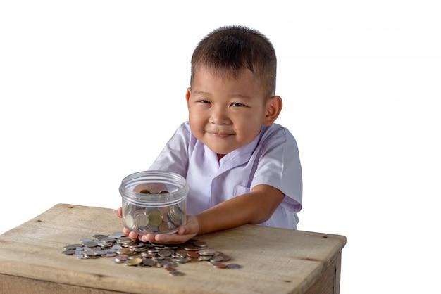 De leuke aziatische landjongen heeft pret met muntstukken in glaskom die op wit wordt geïsoleerd
