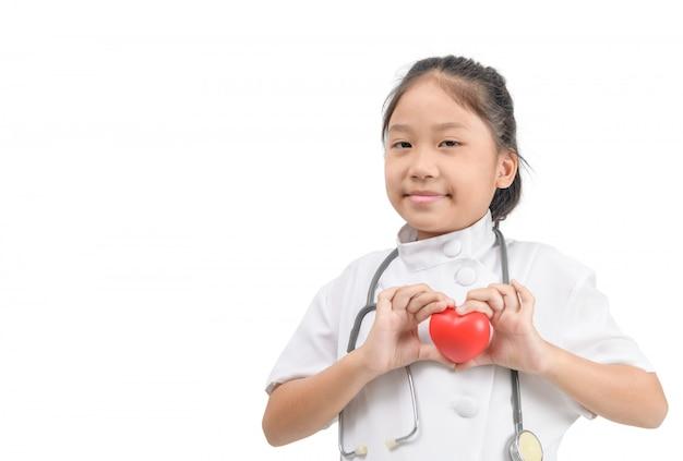 De leuke aziatische meisjes toekomstige arts kleedde zich met stethoscoop en toont rood hart